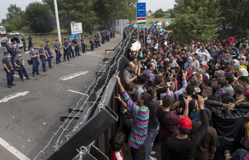 Migrants stand in front of a barrier at the border with Hungary near the village of Horgos